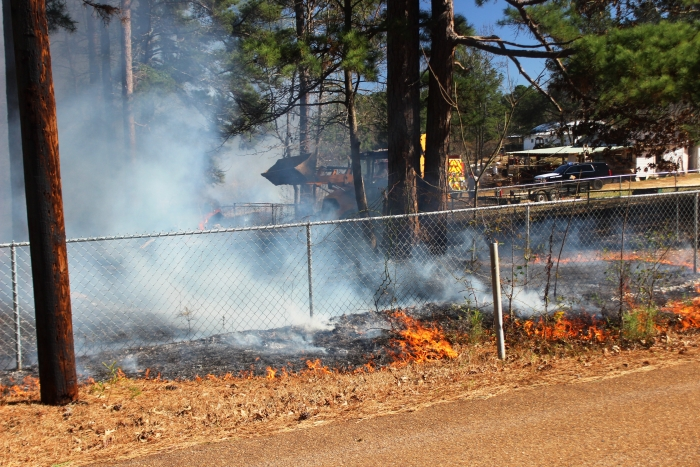 Firefighters and other emergency officials work to put out a grass fire on Corvette Lane in Queen City on Monday.